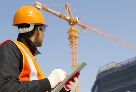 construction worker on location site with crane on the background