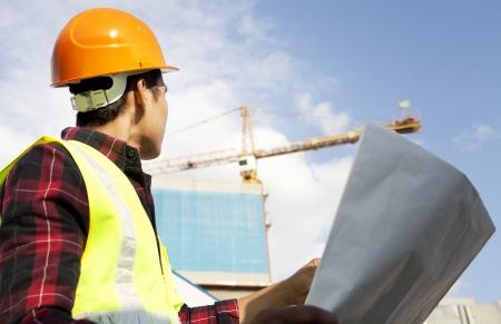 Photo pour Engineer builder with blueprint at construction site - image libre de droit