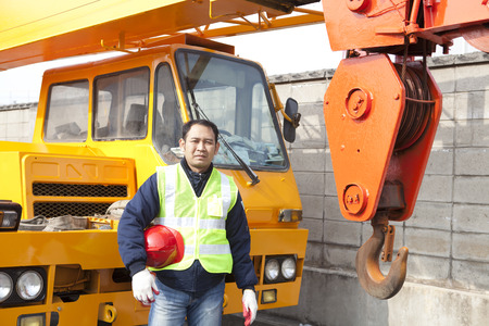 Photo for Driver crane truck posing next to the huge mobile crane with holding safety helmet - Royalty Free Image