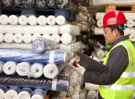 Textile factory foreman auditing raw material fabrics in warehouse