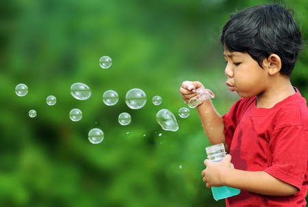 Cute young boy playing with bubbles