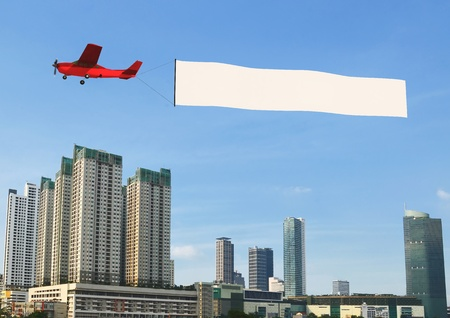 Photo pour Airplane banner pulled by airplane flying over a modern city building - image libre de droit