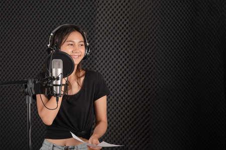 Photo pour teenage female singer in music studio record room - image libre de droit