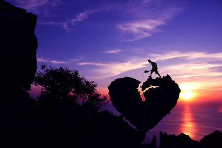 Man shoveling stone to repair the broken heart shape rock on the mountain with purple sky sunset.Silhouette Valentine background concept.