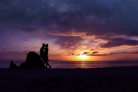 Photo pour Silhouette couple kissing on the beach  with million stars galaxy and purple sky sunrise background - image libre de droit