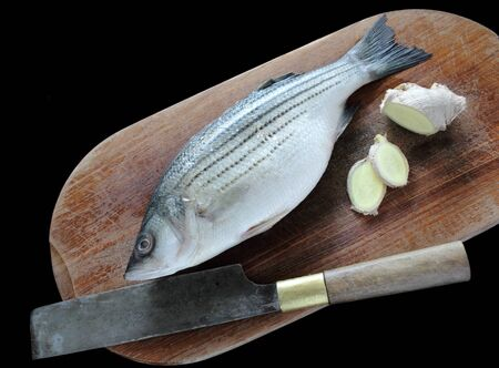 a fresh striped bass and ginger, two ingredients for classic Chinese steamed fish on a cutting board with a knife