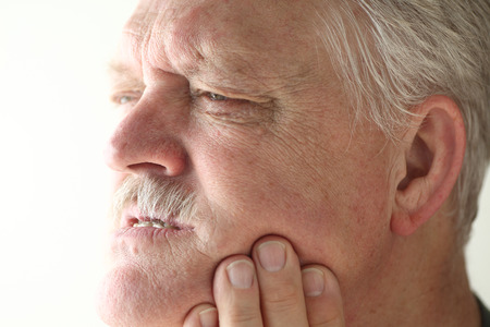 Senior man shows area of pain on his jaw with his fingers.