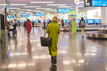 Photo pour Vienna, Austria - March 10, 2020: A woman in a green coat is walking along the premises of the city's airport. - image libre de droit