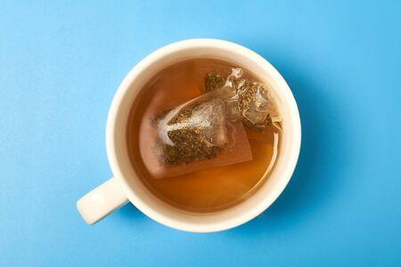 Photo pour Tea bag in a white cup on a blue background. Making delicious herbal tea. - image libre de droit