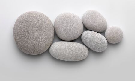 Several pebbles together on gray background with shadow