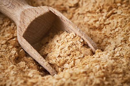 Closeup of nutritional brewers yeast flakes with wooden scoop