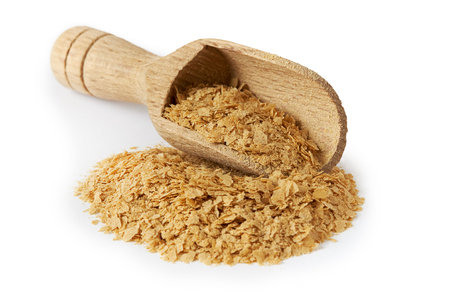 Nutritional brewers yeast flakes in wooden scoop isolated on white background