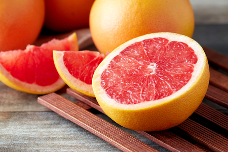 Foto de Fresh raw grapefruit (citrus x paradisi) on wooden background - Imagen libre de derechos