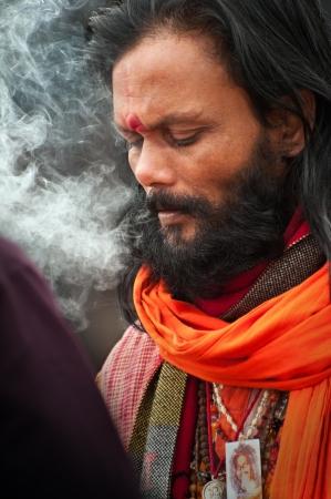 SHANTINIKETAN, INDIA - DECEMBER 25: An unidentified baul folk singer takes a smoke break during the annual Poush Mela fair on December 25, 2012 in Shantiniketan, West Bengal, India.