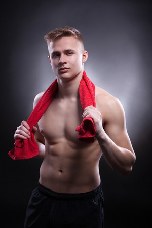 A man with red cloth after the sports workout stands in the studio on the black background