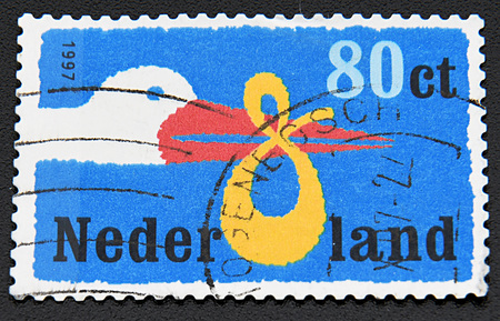 GRANADA, SPAIN - NOVEMBER 30, 2015:   Stamp printed in Netherlands dedicated to Birth Announcement shows the stork bears the baby, 1997.