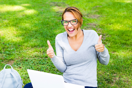 beautiful woman celebrating success news with arms up in a park