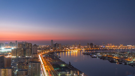 Photo for Cityscape of Ajman from rooftop from day to nigh transition timelapse with lake. Ajman is the capital of the emirate of Ajman in the United Arab Emirates. 4K - Royalty Free Image
