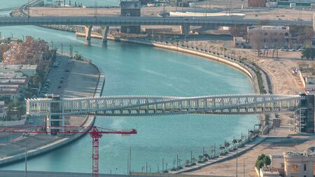 Photo for Dubai water canal with footbridge during sunset aerial timelapse from Downtown skyscrapers rooftop. Floating boats and construction site with cranes - Royalty Free Image