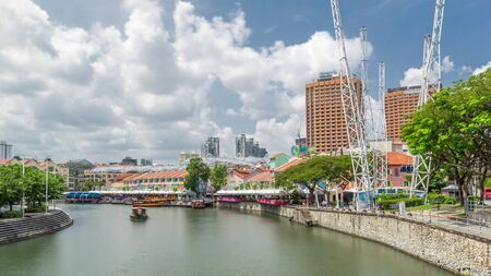 Photo for Tourist boats docking at Clarke Quay habour timelapse hyperlapse with colorful houses. Clarke Quay is a historical riverside quay in Singapore, located within the Singapore River Planning Area. - Royalty Free Image