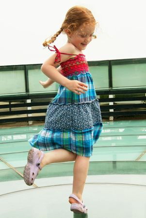 A Little Girl Dances in a Red and Turquoise Dress