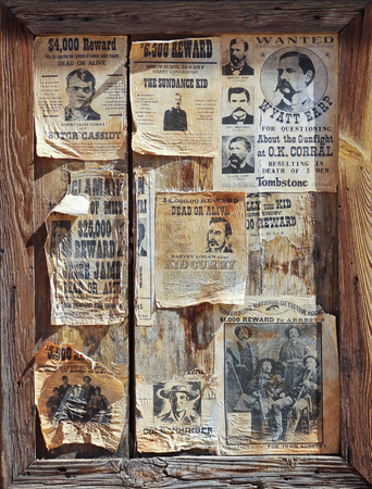 A weathered wooden frame full of assorted wanted posters of notorious outlaws of the Old West.