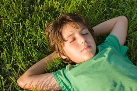 teenager boy relaxing on green grass lawn