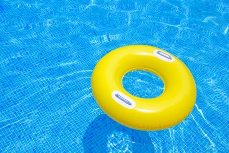 rubber ring floating in transparent blue tiled pool