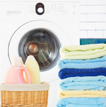 Pile of colorful towels  with detergent and washing machine in bathroom