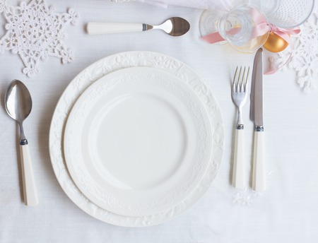 Plates and utensils on white tablecloth with christmas decorations