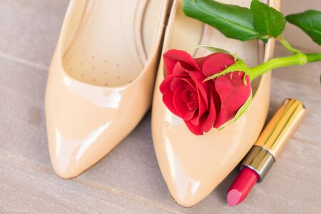 Nude colored high heels still life with red rose bud and lipstick
