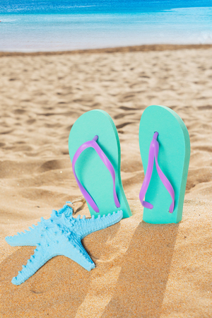 Summer beach fun - summer sandals with starfish in beach sand