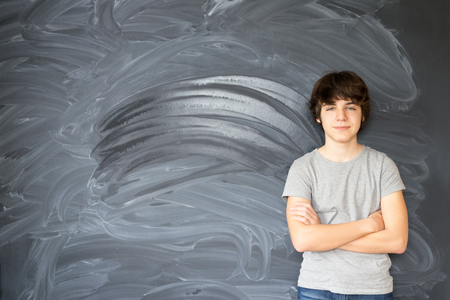 Boy standing with empty black board in background