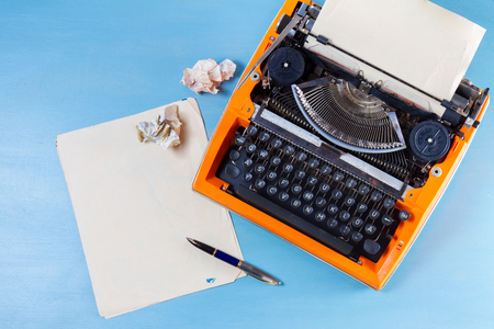 Photo pour Workspace with orange vintage typewriter and empty paper on blue wooden background - image libre de droit