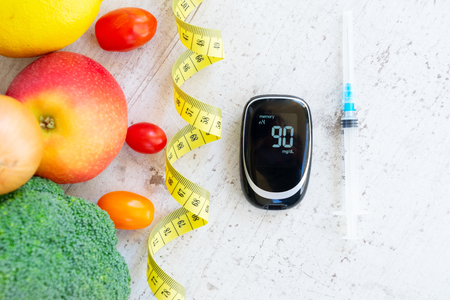 Foto de raw vegetables with blood glucose meter and insulin syringe, diabetes healthy diet concept - Imagen libre de derechos