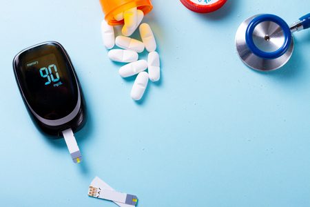 Foto per White pills in orange bottle with blood glucose meter on blue  with copy space - Immagine Royalty Free