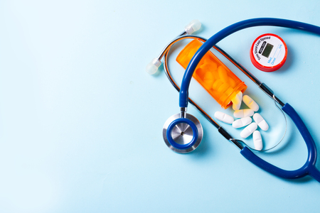Foto de White pills in orange bottle with stethoscope on blue  with copy space - Imagen libre de derechos
