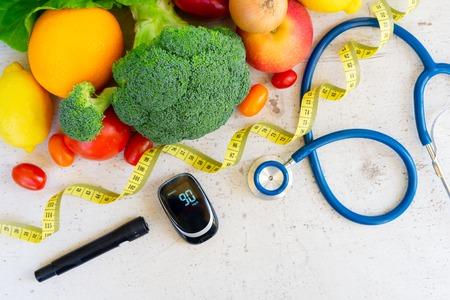Photo pour Raw vegetables with blood glucose meter, lancet and stethoscope, , diabetes healthy diet concept - image libre de droit
