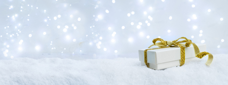 Photo for White christmas. gift box with golden ribbon bow in snow banner - Royalty Free Image