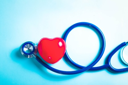 Photo pour Healthcare concept - stethoscope and red heart on blue background, top view, toned - image libre de droit