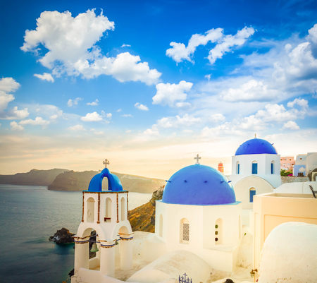 Photo for Traditional white Greek village Oia of Santorini, with blue domes of churches in sunset light, Greece, toned - Royalty Free Image