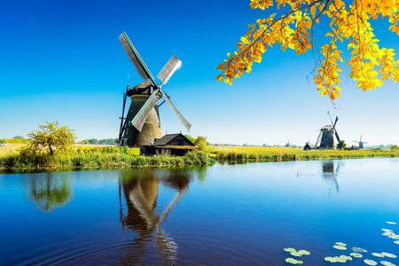 Photo for traditional dutch windmill with reflection at water, Kinderdijk at fall day, Netherland - Royalty Free Image