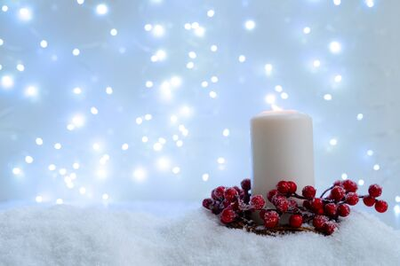 Photo for White christmas - glowing candle in snow, blue night with lights in background. Happy Christas and holidays concept. - Royalty Free Image