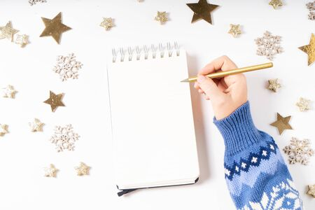 Foto de Wish list for Cristmas and New Year. Holiday decorations and ruled notebook with wish list on white desk, flat lay top view - Imagen libre de derechos