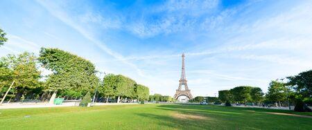 Photo pour Paris Eiffel Tower over green grass lane in Paris, France. Web banner format. Eiffel Tower is one of the most iconic landmarks of Paris. - image libre de droit