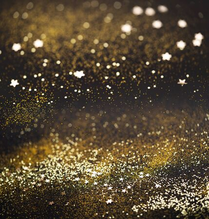 Photo pour Beautiful Christmas light background. Abstract glitter bokeh and scattered sparkles in gold, on black square background - image libre de droit