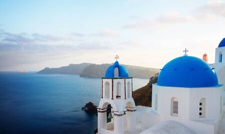 Photo for traditional greek village Oia of Santorini, with blue domes of churches in sunset light, Greece, panorama - Royalty Free Image