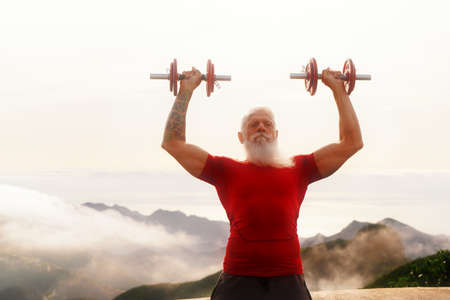 Senior man with white beard doing sport exercises with dumbells outdoor, close up view, healthy and happy lifestyle concept