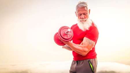 Senior man with white beard doing sport exercises with dumbell outdoor, close up view