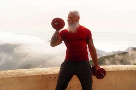 Senior man with white beard doing sport exercises with two dumbells outdoor, close up view, healthy and happy lifestyle concept